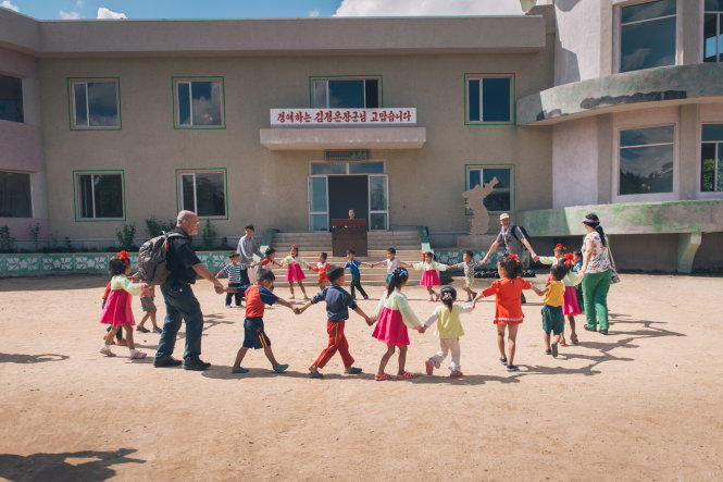 Du khách nước ngoài vui đùa cùng các em nhỏ tại một trường mẫu giáo trong một hợp tác xã nông nghiệp